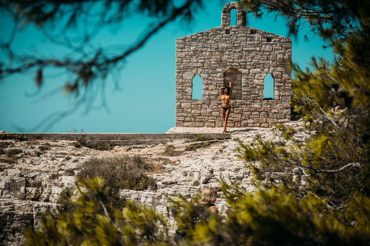 Young Woman Standing In Bikini Against Stone Wall