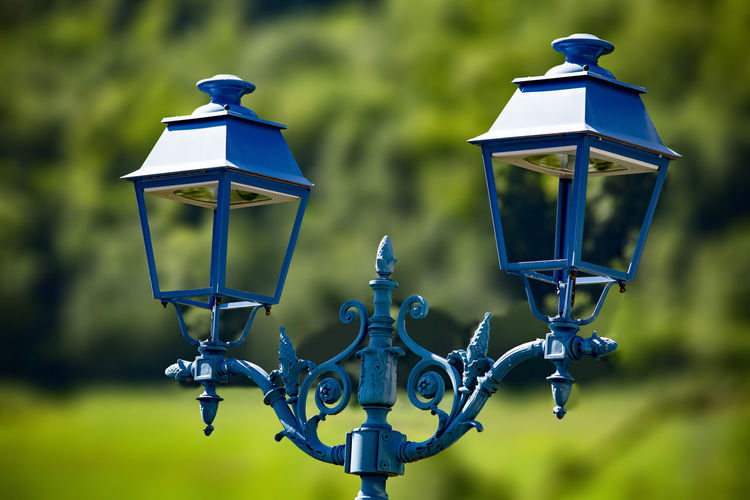 Close-up of lamp against blue sky
