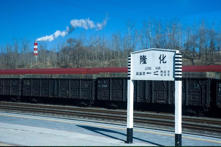 Information sign by railroad tracks against blue sky