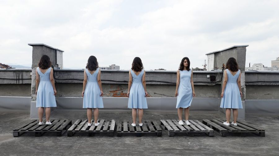 Rear view of women standing on railing against sky