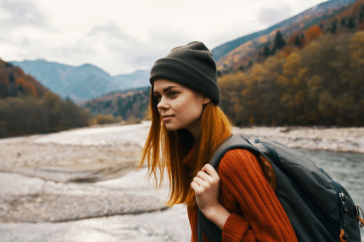 Portrait of beautiful woman standing against mountains