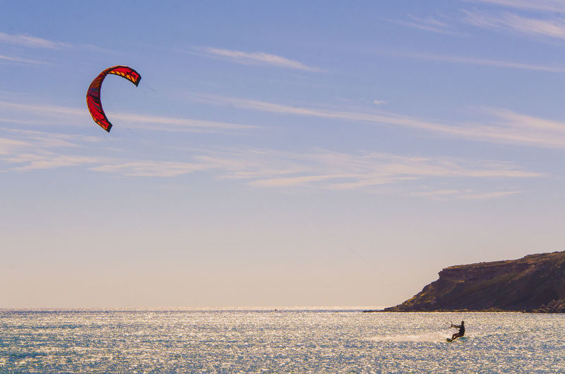 Person kiteboarding in sea against sky