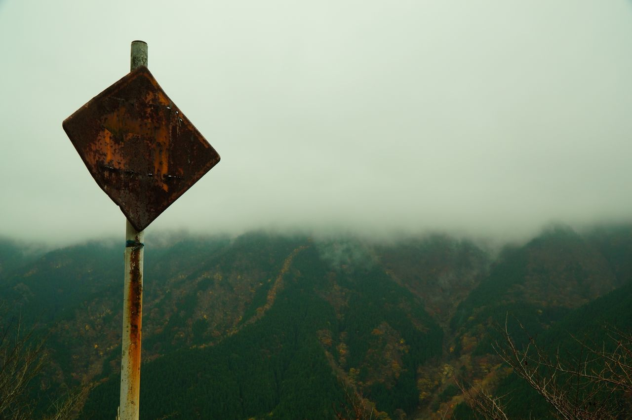 Low Angle View Of Rusty Metal Pole Against Mountains