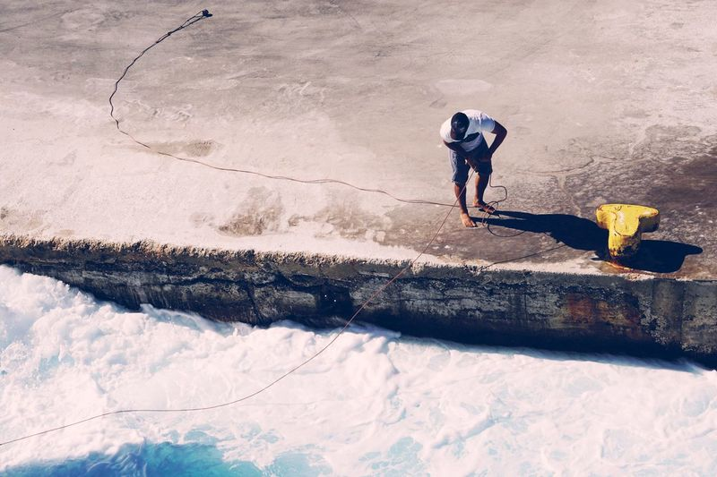 High angle view of man standing on pier