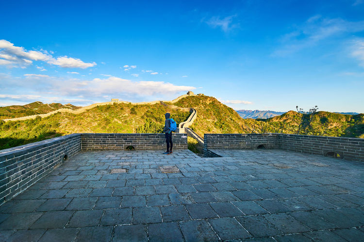 Man looking at view while standing at great wall of china against sky