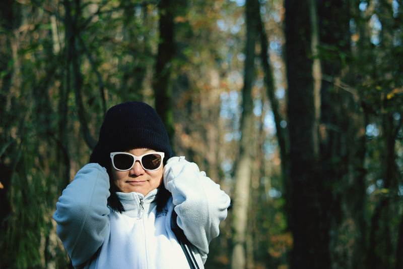Portrait of man wearing sunglasses standing in forest