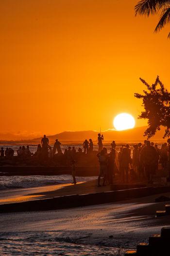 People enjoying at beach during sunset