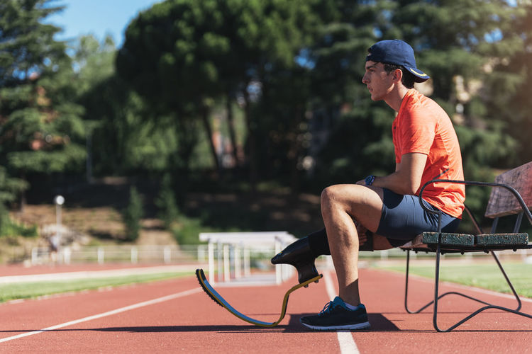 Side view of young athlete with prosthetic leg sitting on bench at running track