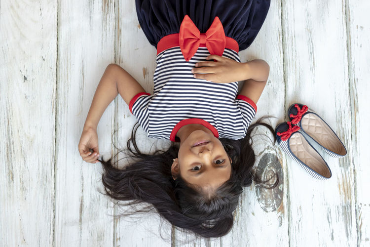 High angle portrait of girl lying on hardwood floor