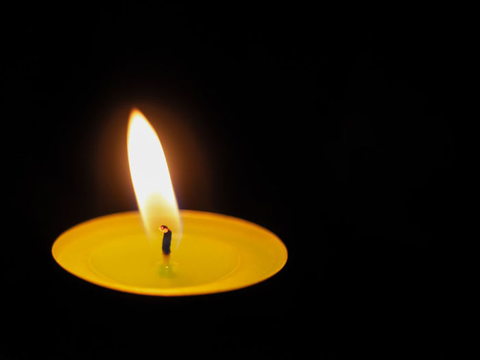 Candle for the deceased to remember Burning Burning Candles EyeEmNewHere Mourning The Week On EyeEm Tranquility Black Background Burning Candle Candle Flame Candle Light Candle Light Beauty Candle Lighting  Candle Lights Close-up Compassion Compassionate Flame Glowing Heat - Temperature Illuminated Luminosity No People Respect For The Deads Yellow