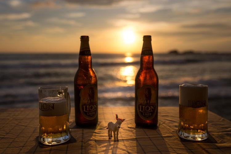 Glasses on beach against sky during sunset