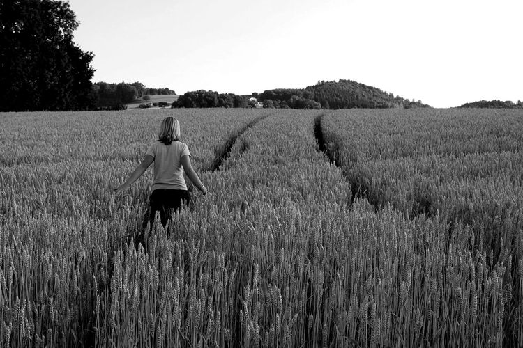 Rear view of woman standing in wheat field
