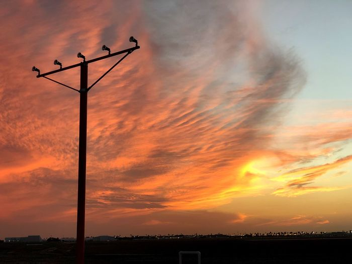 Low angle view of silhouette telephone pole against dramatic sky during sunset