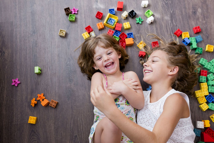 High angle view of happy siblings playing amidst toy blocks on parquet floor