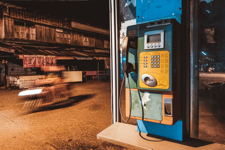 Close-up of pay phone on street at night