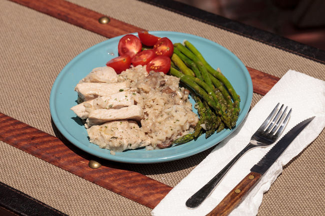 Sauteed pork and asparagus with mushroom risotto meal on a rustic dinner plate Comfort Food Dinner Meal Pork Asparagus Carbohydrates Holiday Meal Hot Meal Mushroom Mushroom Risotto Plate Plate Of Food Risotto Tomato Vegetable White Meat