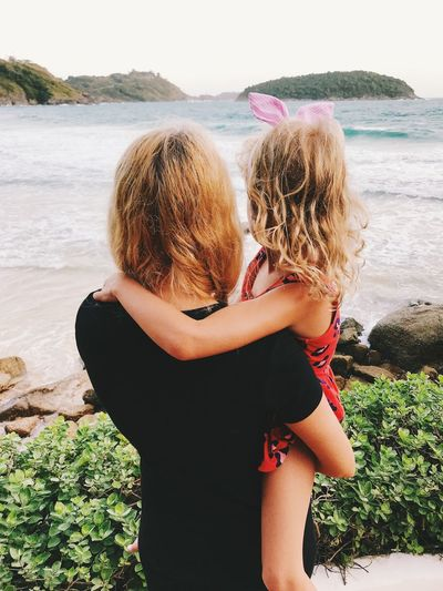 Mother and daughter looking at sea