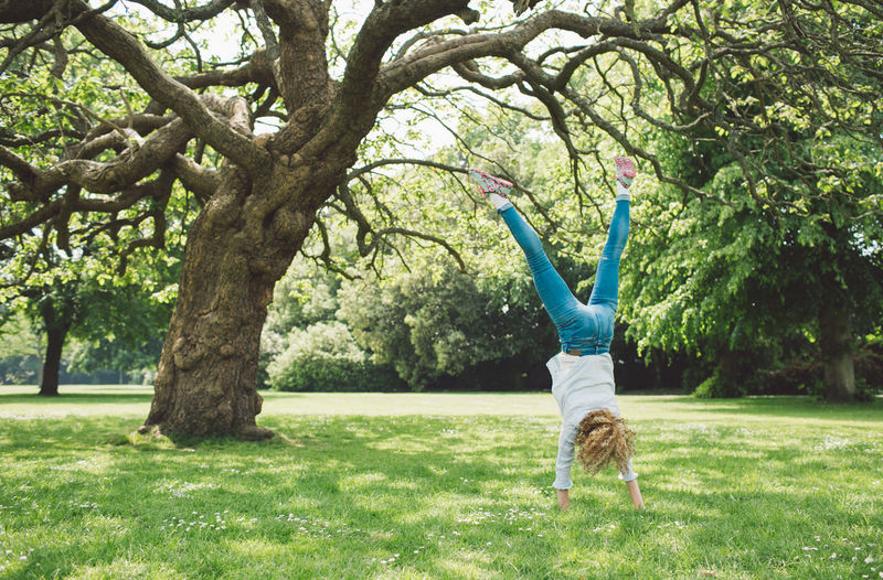 Woman doing handstand on grassy field