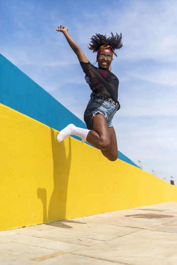 Portrait of cheerful young woman jumping against wall