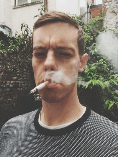 Close-up of young man smoking outdoors