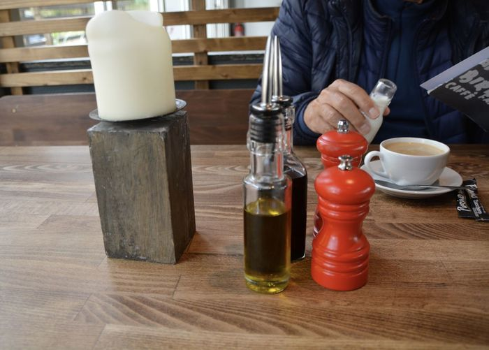 Person with condiments on table