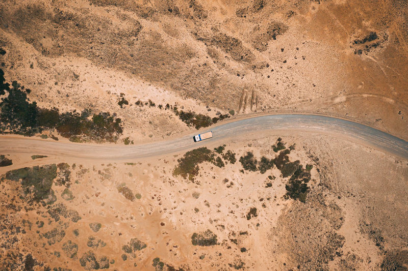 This is an aerial drone camera shot of the main road and vehicle driving during sunset. Road Path Way Dirty Field Above Aerial View Gravel Road Transportation Industry Dusty Rural Countryside Drone  Nature Dirt Track Drive Car Gravel Landscape Terrain Off-roading Curvy LINE Desert Arid Dry Curve Mountain Over Birdseye Remote Dangerous Surface Top Fuerteventura Volcanic  Sand Sandy Vehicle Truck Going Driving Riding Follow Spotted Extreme Terrain High Angle View