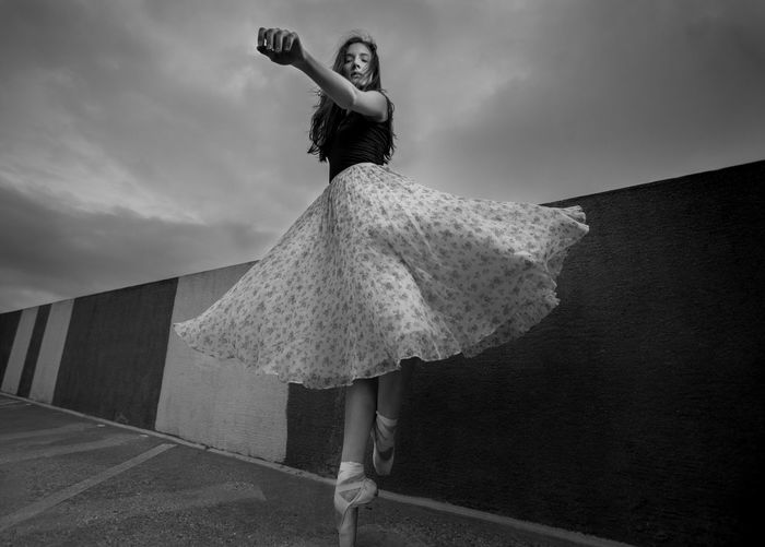 Full length of woman ballet dancing against sky