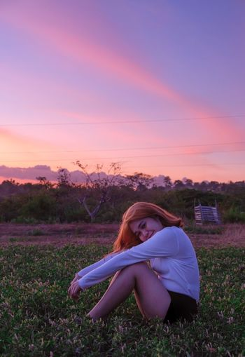 Woman sitting on field during sunset