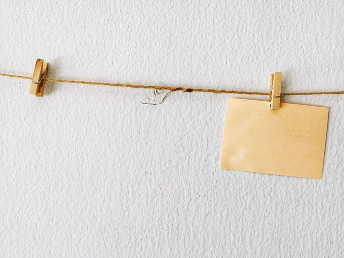 Close-up of clothespins hanging on rope against wall