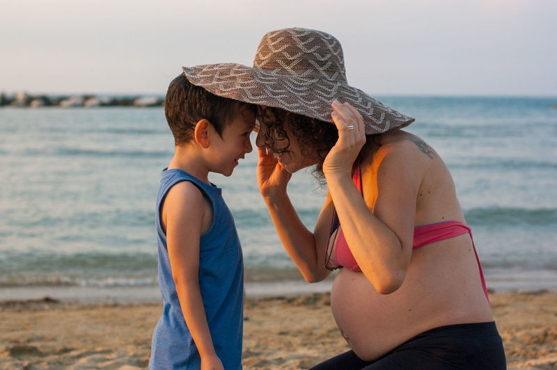 Smiling pregnant mother and son against sea at beach
