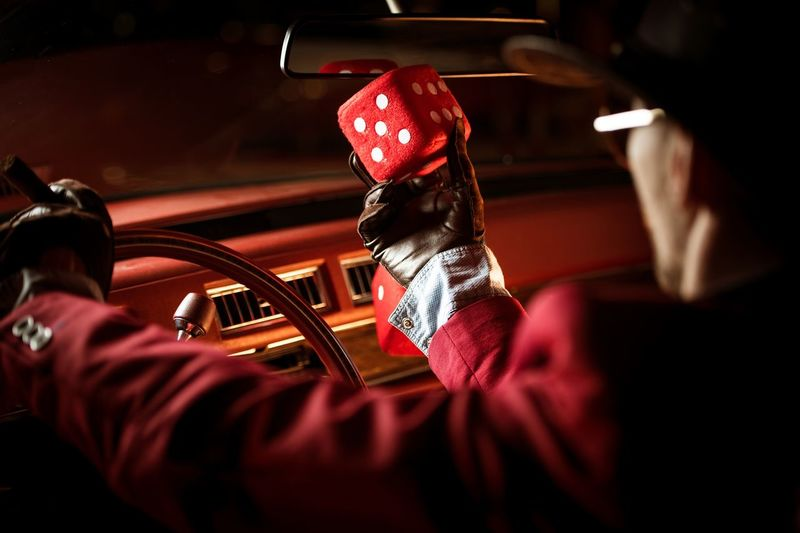Man Holding Dice In Car At Night