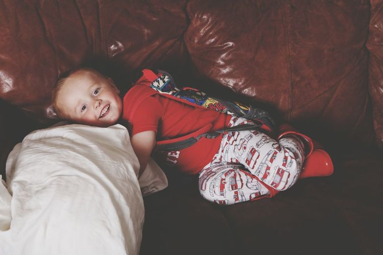 Boy Lying On Sofa And Smiling