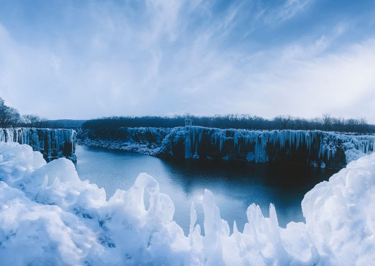 Panoramic view of frozen lake against sky during winter