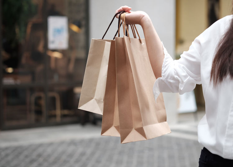 Midsection of woman holding shopping bags