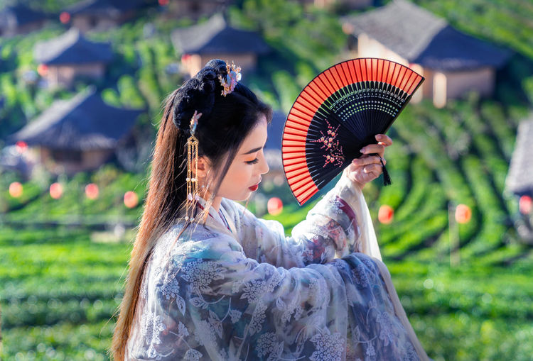 Beautiful woman in traditional clothing holding hand fan sitting at field