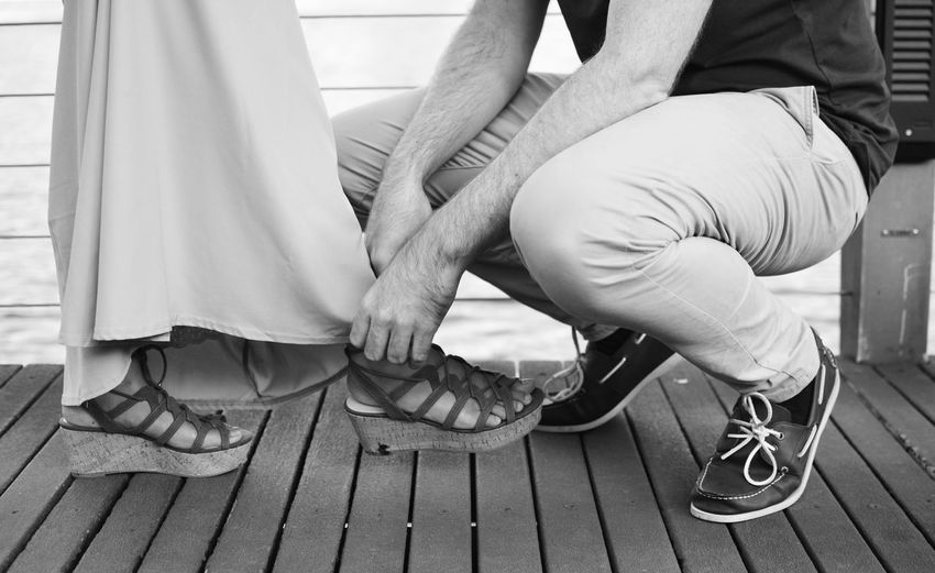 Low Section Of Man Tying Woman's Shoes