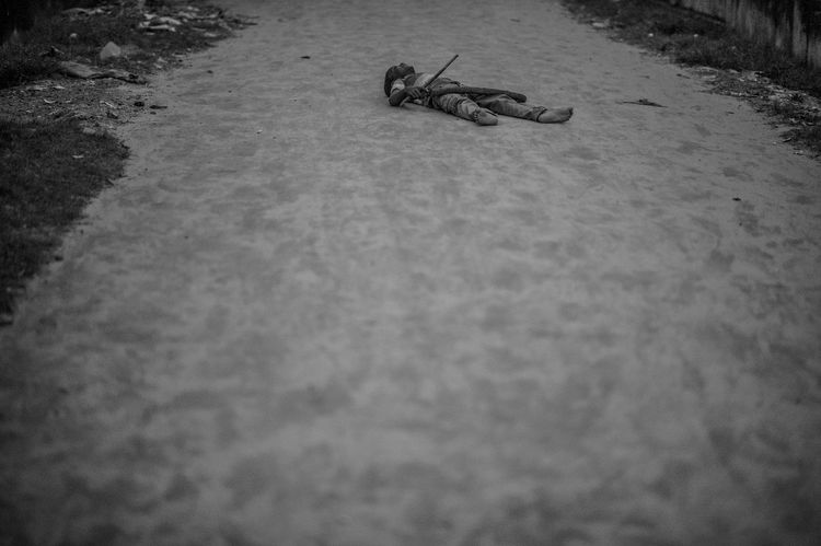 The world is a stage And we are all actors. A little boy from the nearby slum lies on the ground, pretending to be dead. or maybe dead tired. Boy,  Close-up Day Lying On The Floor Monochrome Outdoors Selective Focus Street Photography