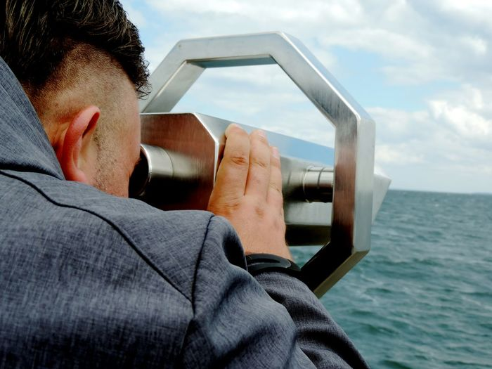 Close-up of man looking through coin-operated binoculars against sea