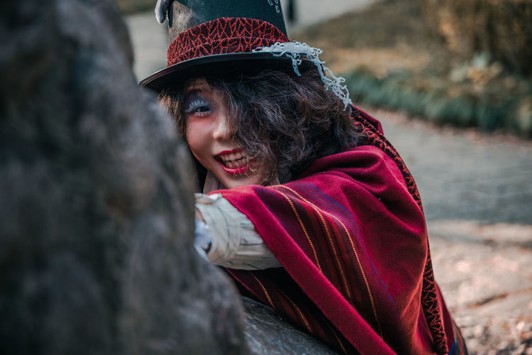 Portrait of man cosplaying mad hatter looking into camera outdoors