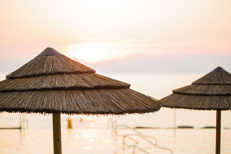 Thatched Parasols At Beach Against Sky During Sunset