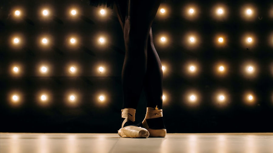 Low section of female ballet dancer standing on stage floor against illuminated lights