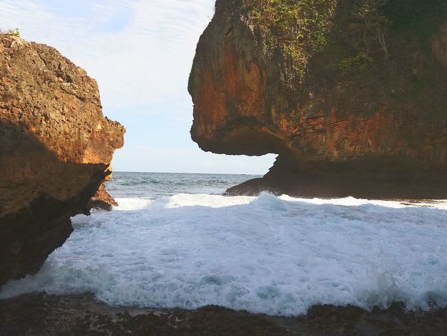 Wave and rock formation EyeEm Selects Sea Rock - Object Rock Formation Beach Cliff Nature Water Wave Landscape No People Scenics Horizon Over Water Sand Outdoors Beauty In Nature Day Sky Landscape_Collection Conected Whit Travel Tranquility Photography Travel Destinations Gunungkidulbeach Yogyakarta, Indonesia
