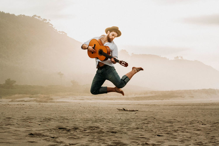 Full length of man jumping while playing guitar at beach