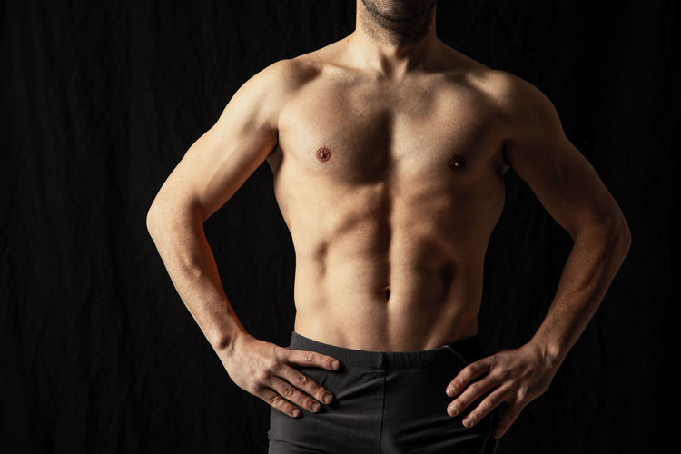 Midsection of shirtless man standing against black background
