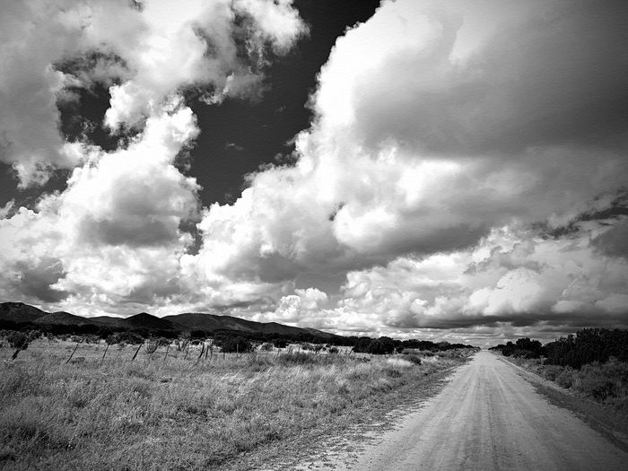 """""""Storm Watch"""" A gathering storm over the Central Highlands of New Mexico. Black And White Black And White Photography Blackandwhite New Mexico Photography New Mexico Clouds And Sky Mountains Storm Cloud Rural Road Cloud - Sky Sky Road Diminishing Perspective The Way Forward Direction Landscape Nature vanishing point Rural Scene"""