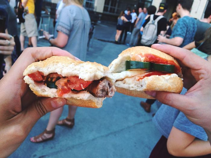 Cropped image of hands holding sandwich on street