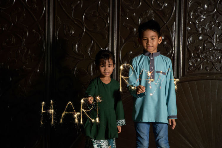 Malay siblings playing fireworks sparkler during ramadan festival