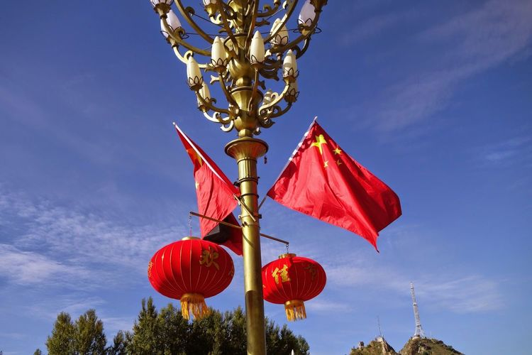Low angle view of lanterns with flags hanging on street light against blue sky during sunny day