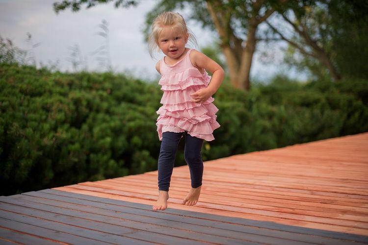 Full length portrait of girl jumping on floorboard