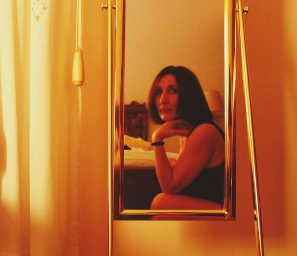 Portrait of young woman reflecting on mirror at home